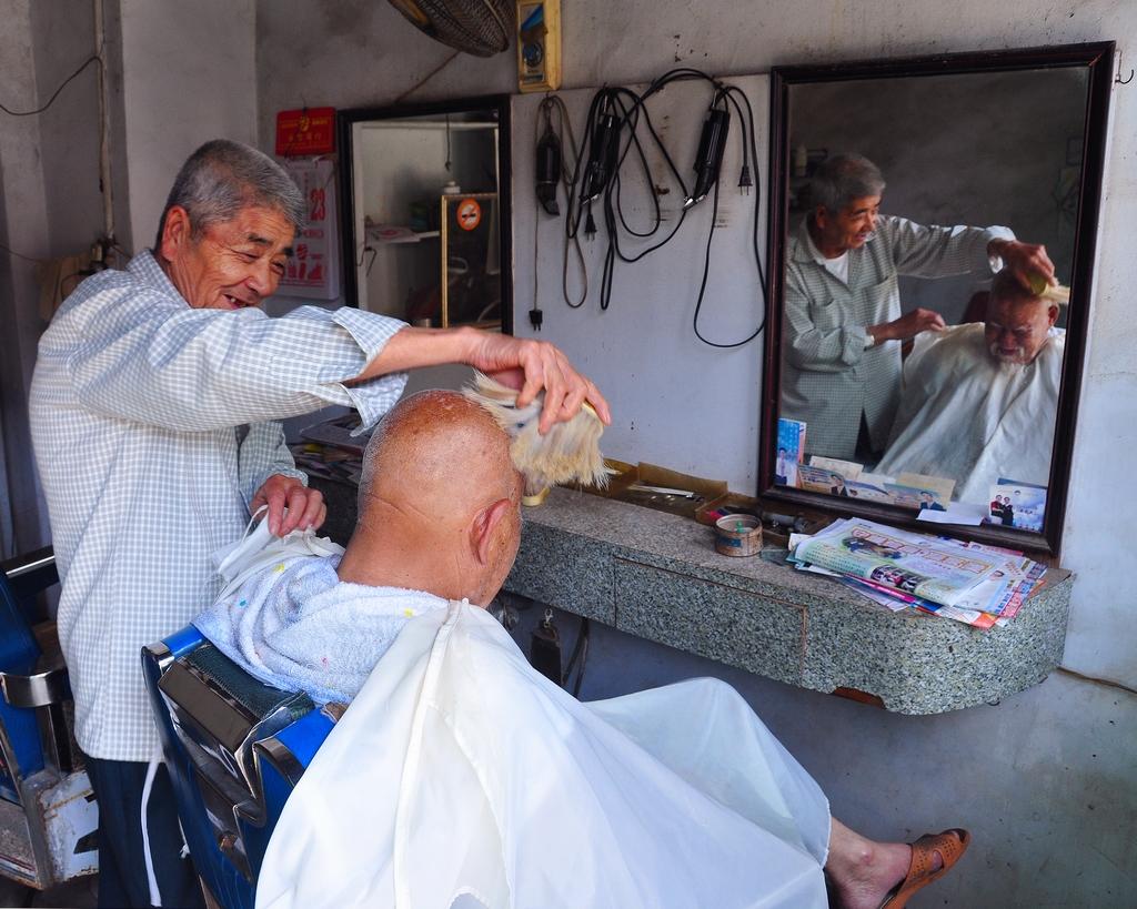 傳統的理髮店中,老顧客依然習慣與理髮師閒話家常,回憶後浦的陳年往事。