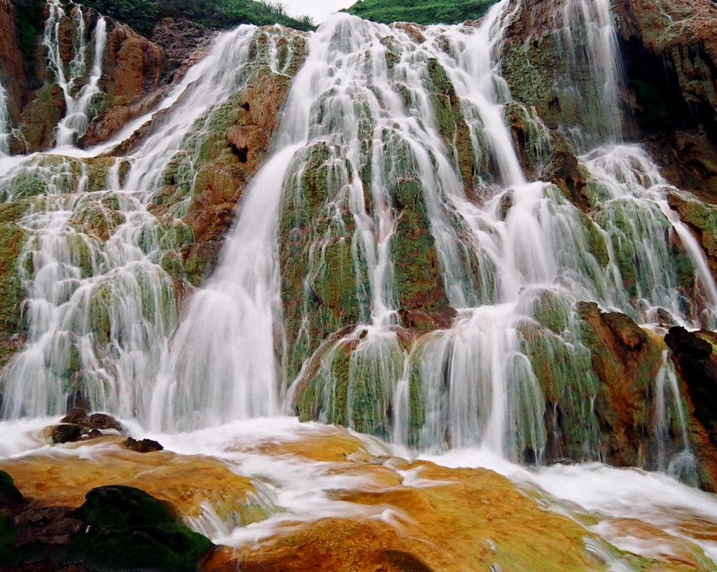 【黃金瀑布(水湳洞地區) 】  圖位於金瓜石往水湳洞的公路邊。因雨水滲入礦區後,與黃鐵礦和硫呻銅礦接觸,經過「氧化還原」與「鐵菌催化」,使瀑布水呈現金黃偏橘色的酸礦水,後人美其名為「黃金瀑布」。