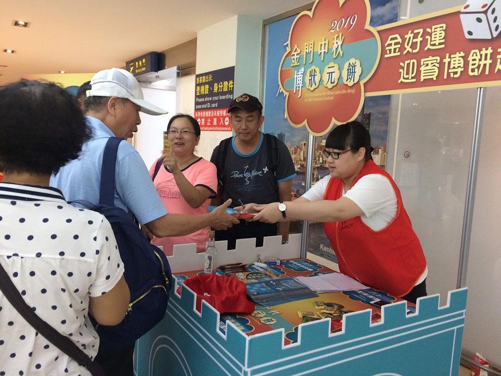 金好運-機場迎賓博餅 蒞金旅客在台灣就能憑機票於起飛前先一步體驗金門博餅的魅力,並獲得各種金門特產彩品  年度:2019  來源:金門縣政府